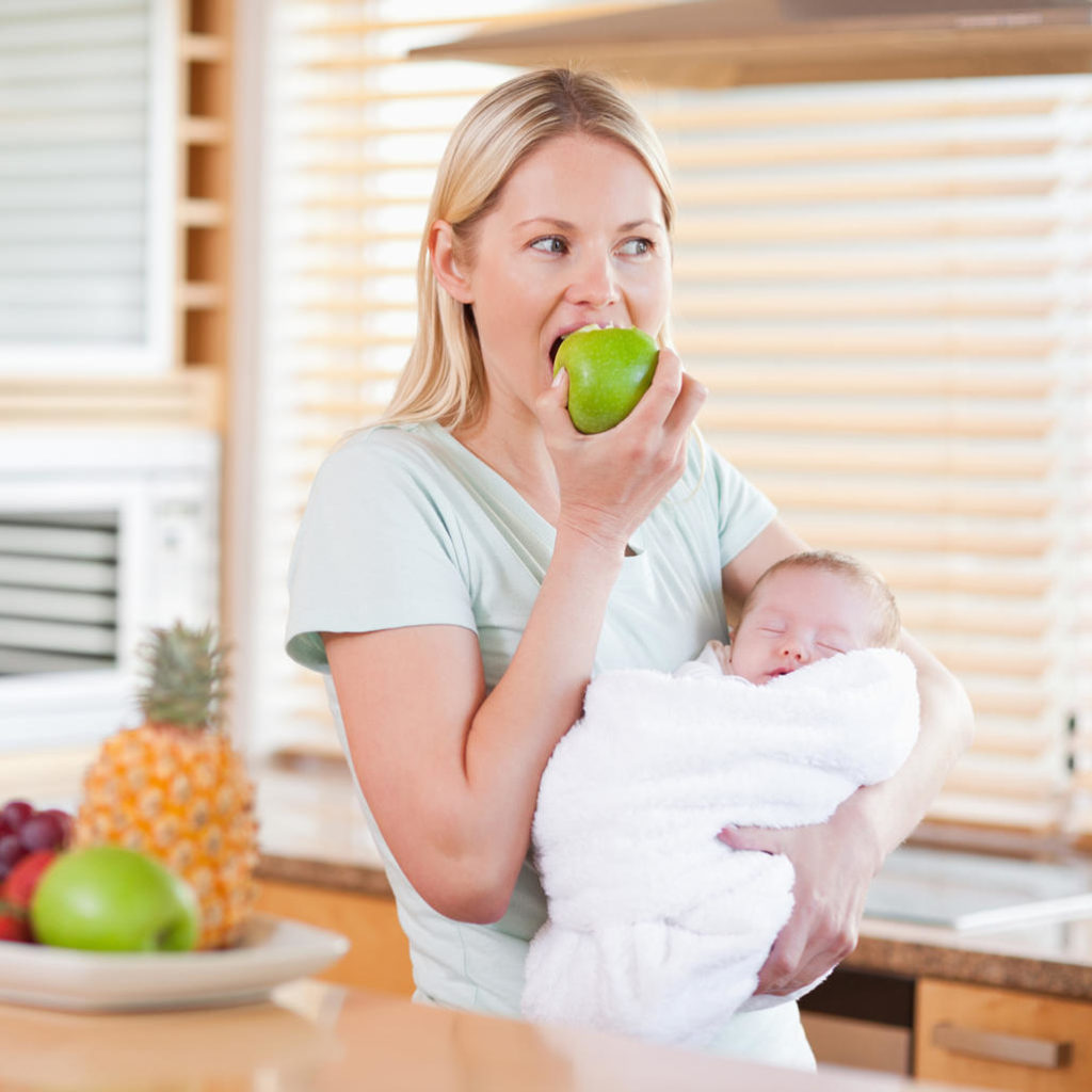 Молодая мама ест яблоко