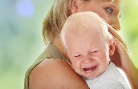 Мама держит плачущего грудничка