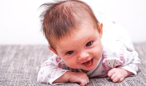 Малыш улыбается лёжа на животе и опираясь на руки