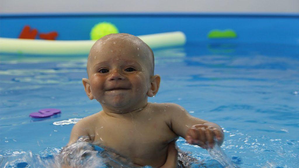 грудничок вынырнул из воды в бассейне