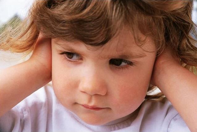 Малыш с вьющимися волосами зажал ладонями уши