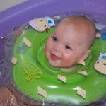 Малыш с зелёным кругом на шее купается