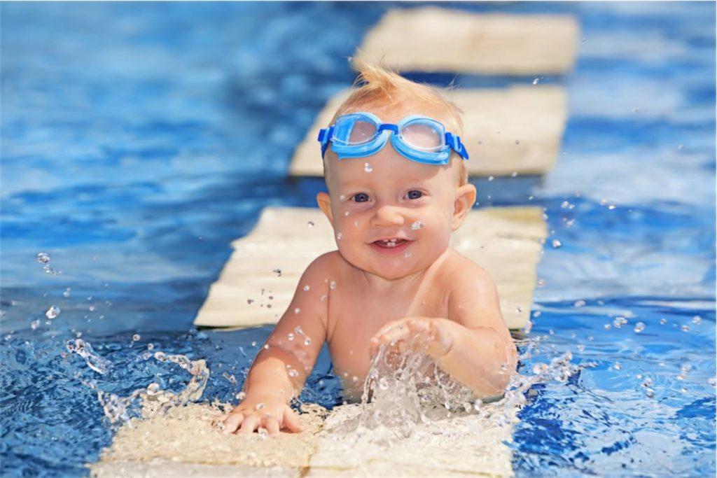 малыш в бассейне с очками на лбу