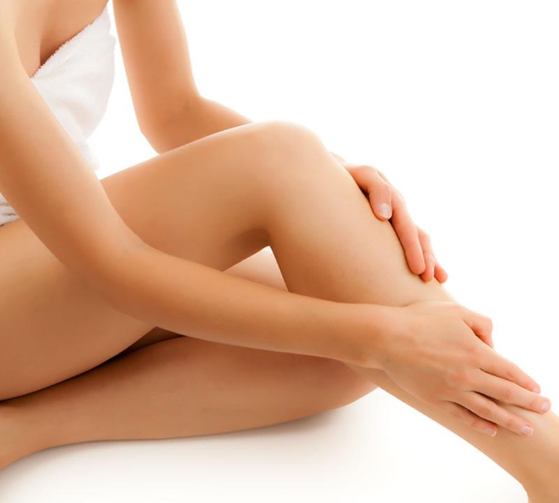 Женщина гладит свои ноги
